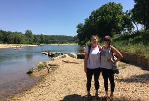 two girls standing next to river